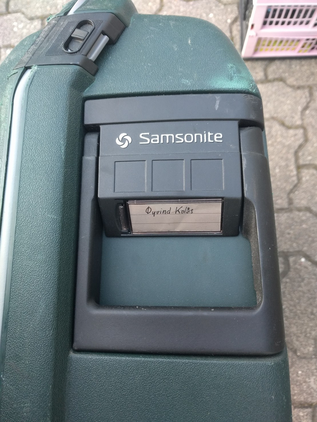 tag on a green suit samsonite case.